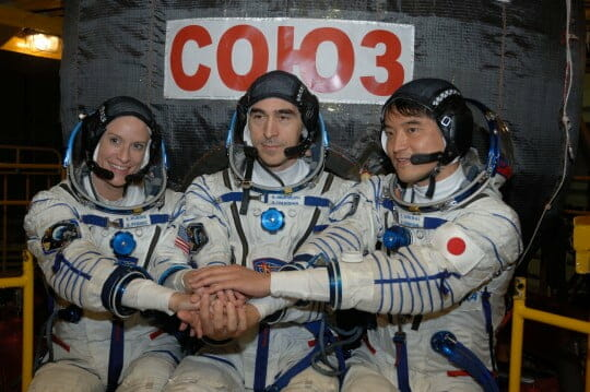 """In the Integration Facility at the Baikonur Cosmodrome in Kazakhstan, Expedition 48-49 crewmembers Kate Rubins of NASA (left), Anatoly Ivanishin of Roscosmos (center) and Takuya Onishi of the Japan Aerospace Exploration Agency (right) pose for pictures June 25 in front of the Soyuz MS-01 spacecraft during a """"fit check"""" dress rehearsal activity. The trio will launch on July 7, Baikonur time, on the Soyuz MS-01 for a planned four-month mission on the International Space Station. NASA/Alexander Vysotsky"""