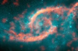 宇宙に現れた巨大な「目」 銀河の衝突による星とガスの波が形成