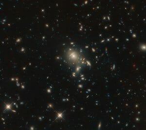 銀河団が作り出す重力レンズの背後に潜む「赤い宝石」