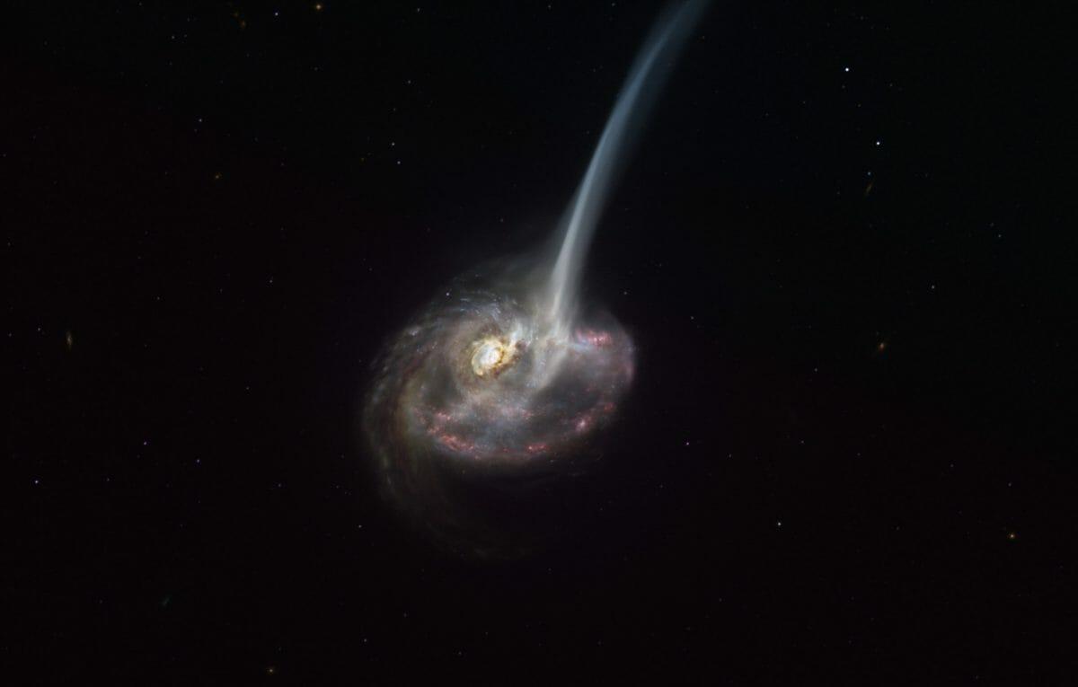 遠方の銀河「ID2299」を描いた想像図。2つの銀河が衝突した際の潮汐力によって長い尾が伸びていると考えられている(Credit: ESO/M. Kornmesser)