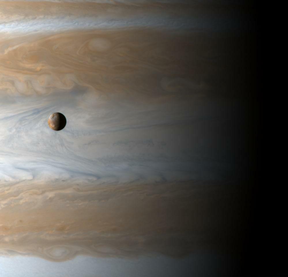 土星探査機「カッシーニ」が木星スイングバイ時に撮影した衛星イオ(左)と木星(背景)(Credit: NASA/JPL/University of Arizona)