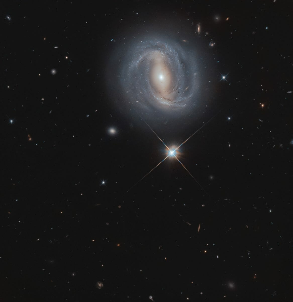 棒渦巻銀河「NGC 4907」(上)と天の川銀河の恒星(中央)(Credit: ESA/Hubble & NASA, M. Gregg)