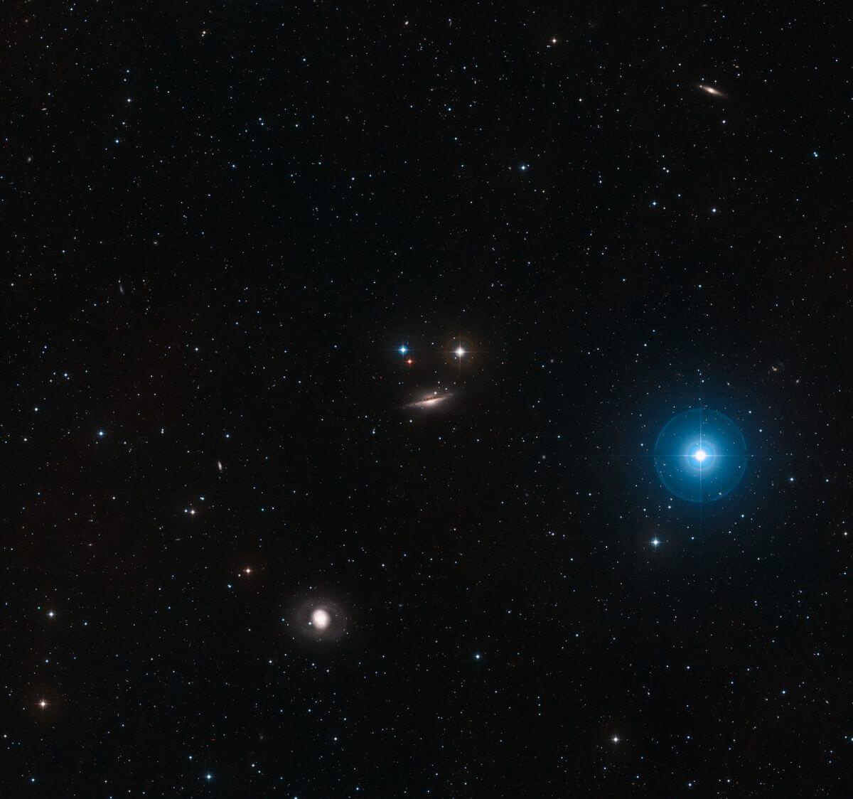渦巻銀河NGC 1055(中央)と周辺の様子(トリミング加工済み、元の画像はこちら)。渦巻銀河M77(NGC 1068)は左下に見えている(Credit: ESO/Digitized Sky Survey 2, Acknowledgement: Davide De Martin)