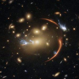 銀河団の重力が歪めた100億光年彼方の銀河の像、ハッブル宇宙望遠鏡が撮影