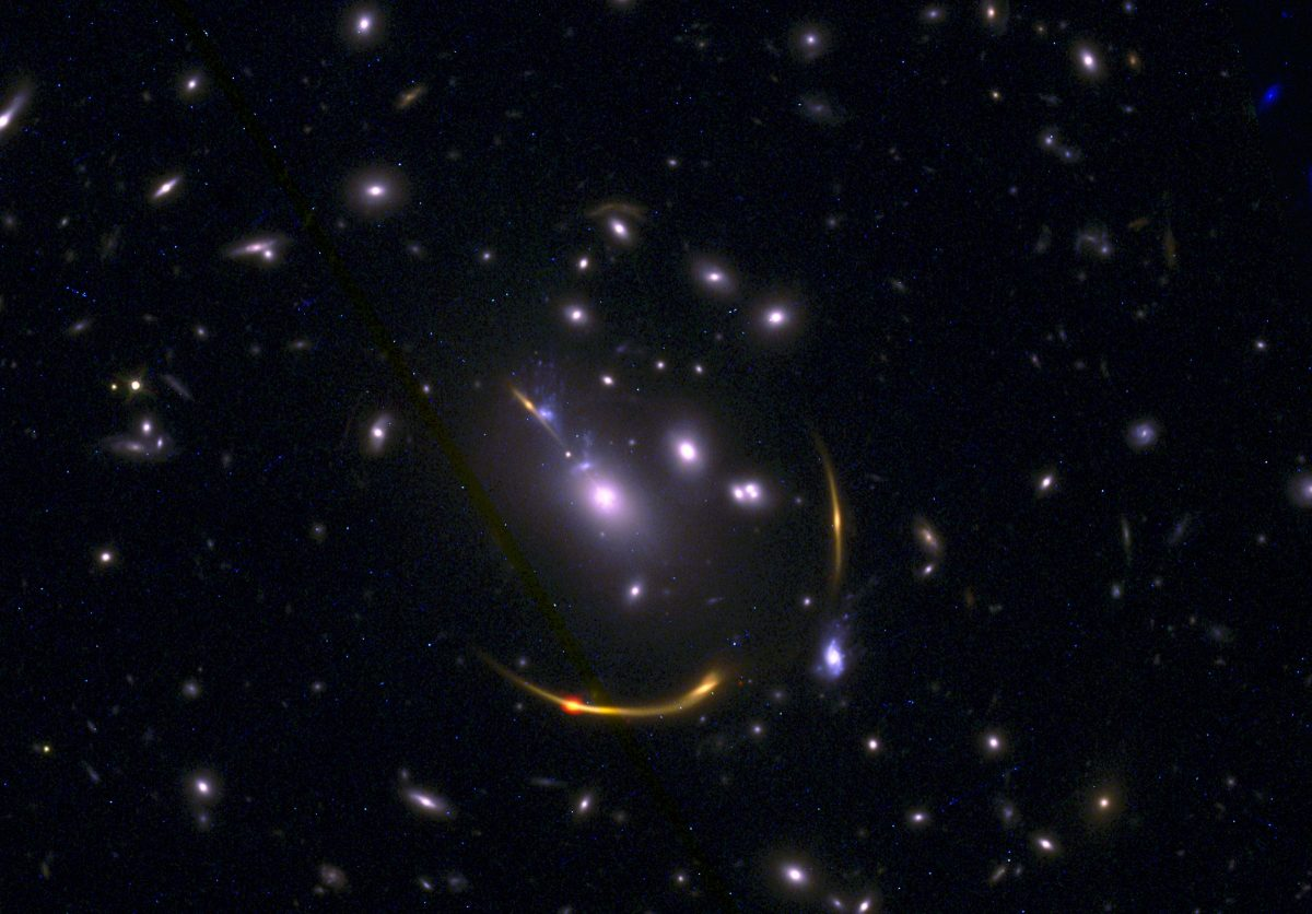 銀河団「MACS J0138」による重力レンズ効果を受けた銀河「MRG-M0138」。画像はハッブル宇宙望遠鏡とアルマ望遠鏡の観測データから作成(Credit: ALMA (ESO/NAOJ/NRAO)/S. Dagnello (NRAO), STScI, K. Whitaker et al.)
