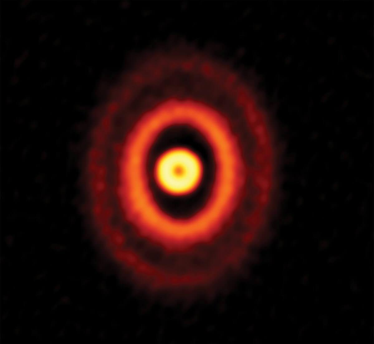 アルマ望遠鏡によって観測された三重連星「オリオン座GW星」を取り巻く3つのリング。最も内側のリングはほぼ正面から、外側の2つのリングはやや傾いた角度から見えているとされる。ここには写っていないが、オリオン座GW星はリングの中心に位置する(Credit: ALMA (ESO/NAOJ/NRAO), Bi et al., NRAO/AUI/NSF, S. Dagnello)
